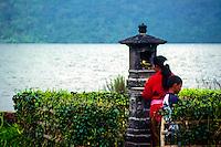 Bali, Tabanan, Bratan. Woman bringing offerings to the temple gods. Ulun Danu temple.