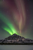 The aurora borealis, also called the northern lights, arcs over the mountains of the Brooks range in Alaska's arctic, situated under the aurora oval.