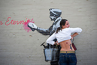 "A street art enthusiast shows off her Banksy inspired tattoo in the Woodside neighborhood of Queens in New York on Monday, October 14, 2013 in front of the fourteenth installment of Banksy's graffiti art, ""What we do in life echoes in Eternity"". The elusive street artist is creating works around the city each day during the month of October accompanied by a satirical recorded message which you can hear by calling the number 1-800-656-4271 followed by  # and the number of artwork.  (© Frances M. Roberts)"