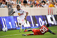 Dane Richards (19) of the New York Red Bulls jumps over a tackle by Danleigh Borman (25) of Toronto FC. The New York Red Bulls defeated Toronto FC 5-0 during a Major League Soccer (MLS) match at Red Bull Arena in Harrison, NJ, on July 06, 2011.