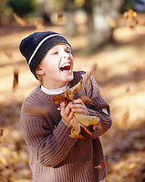 A boy laughing and playing with autumn leaves