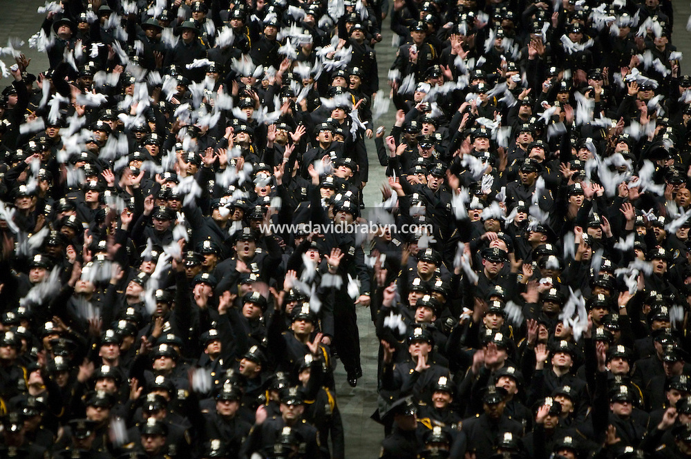 29 December 2005 - New York City, NY - Recruits belonging to the New York Police Department's Class of 2005 throw their white gloves up n the air after graduating, 29 December 2005, in New York City. 1,735 recruits were sworn in during the ceremony.