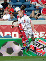 Chicago forward Patrick Nyarko (14) and Toronto defender Richard Eckersley (27) battle for a header.  The Chicago Fire defeated Toronto FC 2-0 at Toyota Park in Bridgeview, IL on August 21, 2011.