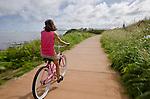 Woman bicycling along a bike path along the coast in Kapa'a, Kauai, Hawaii