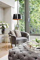 In a modern sitting room, a floor lamp stands behind a tub armchair with pattern cushions and a flower arrangement in a glass vase is placed on a metal side table. Objects on a tray are arranged on an upholstered ottoman in the foreground.