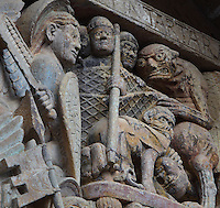 A demon capturing 3 bad monks in a fishing net, and another demon biting a bad monk below, early 12th century Romanesque, carved by the Master of the Tympanum, from the tympanum of the Last Judgement above the portal on the West facade of the Abbatiale Sainte-Foy de Conques or Abbey-church of Saint-Foy, Conques, Aveyron, Midi-Pyrenees, France, a Romanesque abbey church begun 1050 under abbot Odolric to house the remains of St Foy, a 4th century female martyr. The church is on the pilgrimage route to Santiago da Compostela, and is listed as a historic monument and a UNESCO World Heritage Site. Picture by Manuel Cohen
