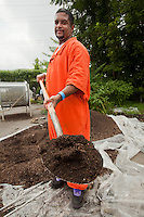 Samuel Soto shows off a shovel of completed and filtered compost outside the old Holmesburg Prison.