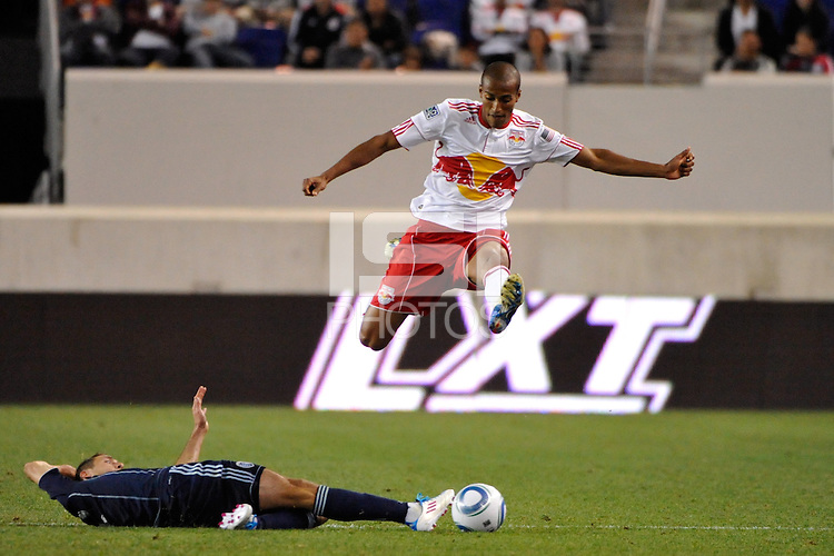 Roy Miller (7) of the New York Red Bulls jumps over the tackle of Davy Arnaud (22) of Sporting Kansas City. The New York Red Bulls defeated Sporting Kansas City 1-0 during a Major League Soccer (MLS) match at Red Bull Arena in Harrison, NJ, on April 30, 2011.
