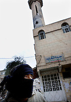 A young man with his face covered for fear of reprisals stands outside a damaged mosque in the eastern Damascus suburb of Sakba. The mosque was damaged during an assault by government forces in their attempt to retake the area from the Free Syria Army. Protests against the ruling Baathist regime of Bashar al-Assad erupted in March 2011. Although they were initially peaceful,  they were violently repressed by the Syrian army and police. In response to being ordered to shoot unarmed civilians, large numbers of men deserted the army and formed the Free Syrian Army. The protest movement has now turned into an armed uprising with clashes between the regular army and the Free Syrian Army taking place in early 2012....