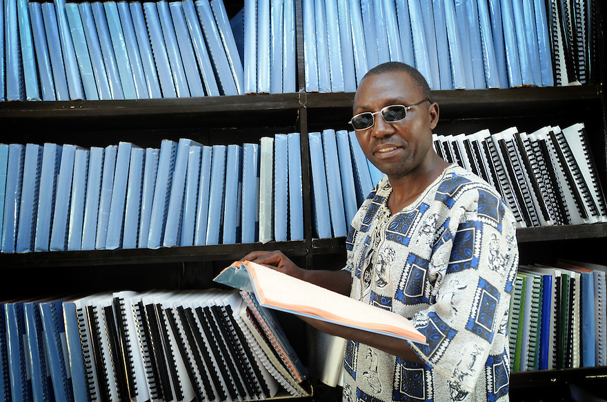 UGANDA BRAILLE BIBLE CASE STUDIES. BENSON NKWASIBWE, HEAD OF THE SPECIAL NEEDS UNIT OF IGANGA SECONDARY SCHOOL, WITH ALL BOOKS OF THE BRAILLE BIBLE, IGANGA,  UGANDA. PHOTO BY CLARE KENDALL. 25/9/13