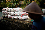 The water from Code River rises due volcanic material filling the river canal, in Yogyakarta, Indonesia, on Wednesday, Nov. 11, 2010. Indonesians fill sand bags to prevent the water from rushing into their homes.