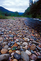 A fly rod rests on stones along the Rock Creek near Missoula Montana.
