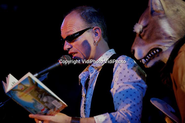 Foto: VidiPhoto..ARNHEM - Kinderboekenschrijver Paul van Loon is zaterdag benoemd tot Officier in de Orde van Oranje-Nassau tijdens de Dolfje Weerwolfjedag in Burgers' Zoo in Arnhem. De loco-burgemeester van Heusden, de woonplaats van Van Loon, spelde hem de hoge onderscheiding op. Paul van Loon is dit jaar 25 jaar schrijver. In die periode schreef hij meer dan 90 boeken en werd hij acht keer winnaar van de Nederlandse Kinderjury. Foto: Paul van Loon leest voor uit eigen werk.