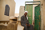 Mohamed Ahmed Ismail in front of his brand-new house at new Qurna; the old door behind him was brought over from his demolished house, where many generations of his family lived.. Luxor, Egypt..Photo: Eduardo Martino