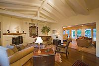 Spanish family room featuring white painted bemed cielings, elegant furnishings, hardwood floors and large windows.