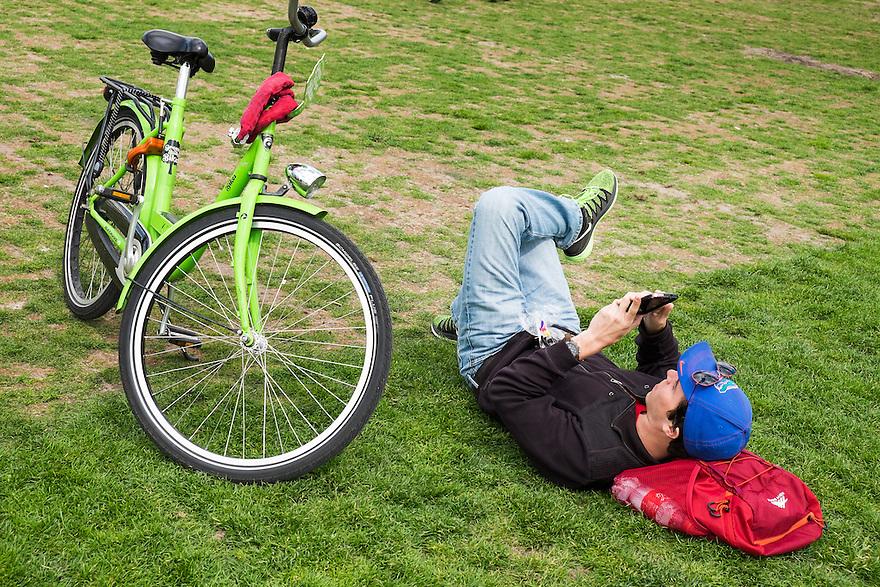 Nederland, Amsterdam, 30 mei 2015<br /> Museumplein. Man, toerist, ligt  in het gras van het Museumplein naast zijn huurfiets en checkt zijn mobieltje<br /> <br /> Foto: Michiel Wijnbergh