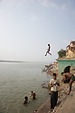 A young boy appears to walk on air as he leaps into the Ganges River, Varanasi, India.
