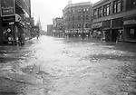 Flood waters in Waterbury cover the junction of South Main and Grand Streets, once better known as Benzine Corner. Merchandise in many of these downtown stores was ruined by the water. Straight ahead are steeples of St. Anne's Church.