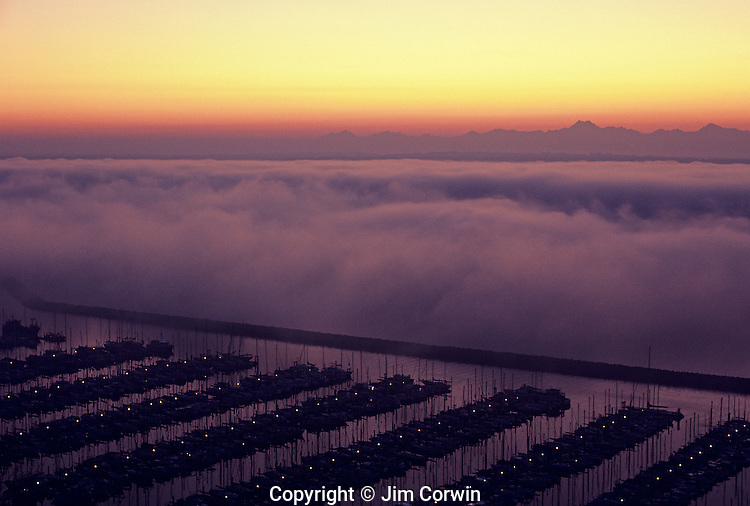 Shilshole Marina from bluff overlooking Puget Sound blanketed in fog with Olympic Mountains at sunset Seatttle Washington State USA