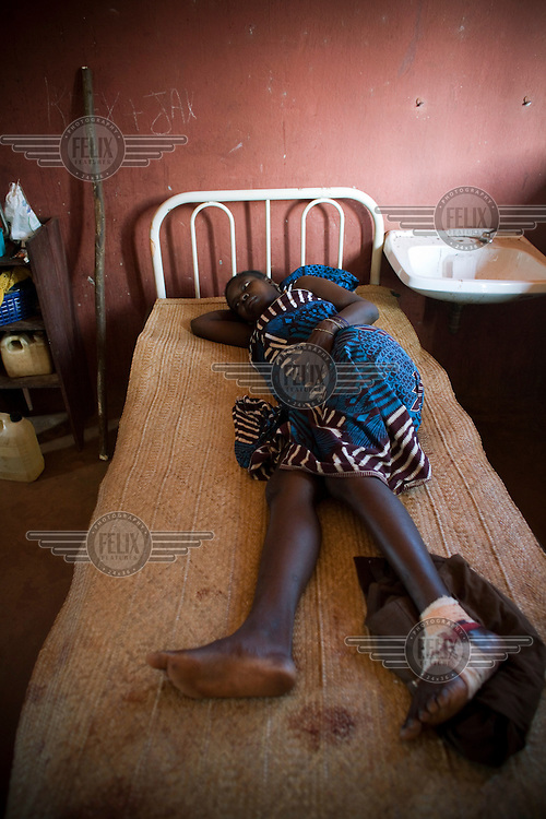 A wounded girl with a bandaged foot lies on a bed in a hospital.