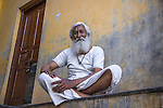 Friendly old hindu man, dressed in white, at his doorstep (Pushkar, India, 2011).<br />