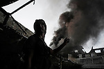 SYRIA, ALEPPO. A Syrian rebel shows with the hand a black coloumn of smoke raising from an abandoned hotel in the Old City of Aleppo on September 24, 2012 ALESSIO ROMENZI