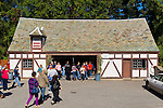 Mill Neck, New York, U.S. 12th October 2013. People visit the Cheese House at the annual Fall Harvest Festival, also known as Apple Fest, which attracts tens of thousands of visitors with its food, crafts, and more, on the grounds of Mill Neck Manor, an historic Gold Coast estate, during Columbus Day weekend. The Tudor Revival style building of wood and stucco has a slate roof with tiles that are biggest along the bottom and become smaller and smaller as they reach the top of the roof, to create an optical illusion that the building is actually bigger than it is. Proceeds benefit the Mill Neck Family of organizations including the Mill Neck Manor School for the Deaf.