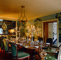 An elegant Georgian dining table is laid for a candlelit dinner in an Empire-style dining room with walls covered in trompe l'oeil classical scenes