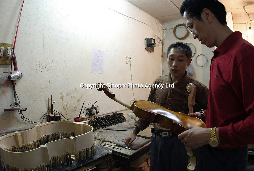 Chen Shunbao, president of the Shanghai Wellsound-Tianyin Violin Factory, examines an unfinished violin with an unamed craftsman at the factory's workshop  in Shanghai, China. Started in 1992 by Mr. Chen who came from a family with four generations of music instruments making experience, the company exports most of its high-end and hand crafted string instruments overseas. China supplies over 90% of the world's high-end music instruments..13-SEP-04