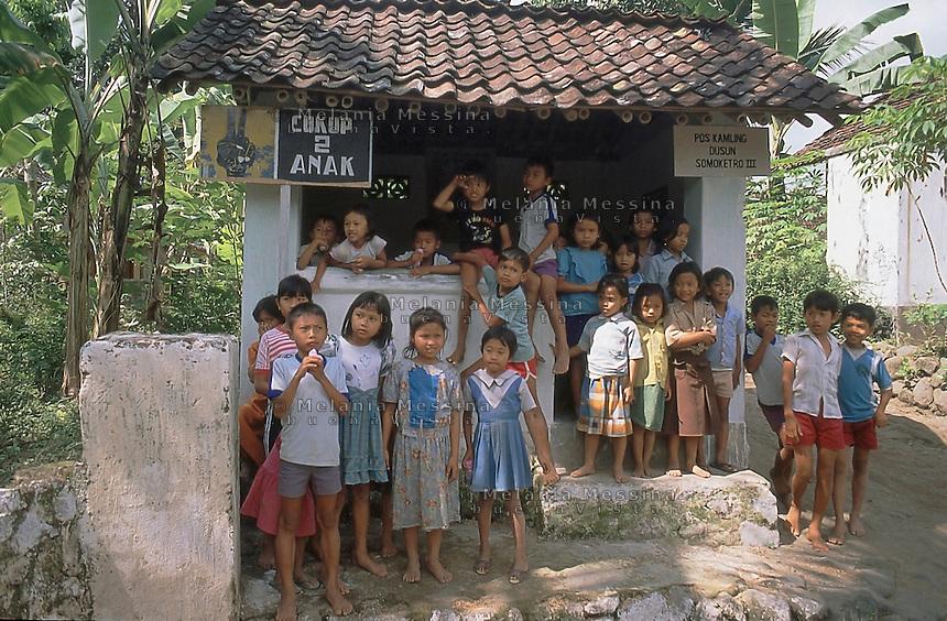 Indonesia; Java, kids under a sign of the government's propaganda that says only 2 children, to raise awareness of birth control.<br /> Indonesia, Giava, bambini sotto un cartello di propaganda del governo con scritto solo 2 figli, per sensibilizzare al controllo delle nascite.
