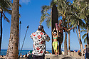 Tourist couple taking photos at Duke Kahanamoku statue at Kuhio Beach Park, Waikiki Beach, Honolulu, Oahu, Hawaii.