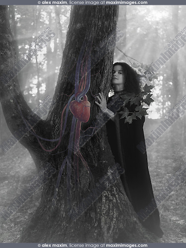 Woman druid in the forest listening to the heartbeat of a tree, artistic conceptual black and white photo illustration