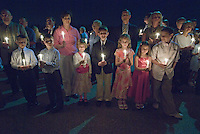 Families holding small Easter candles gather together in the dark to participate in the candle lighting ceremony on Holy Saturday at a Catholic church in Westerville, Ohio.<br />