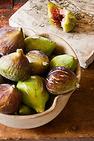 A bowl of freshly picked figs next to a chopping board with an open fig revealing its red flesh
