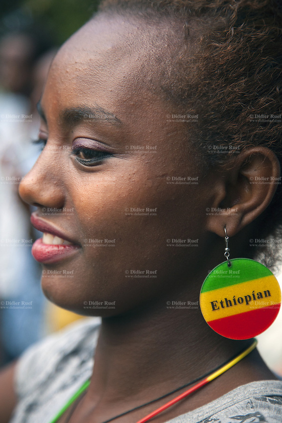 Ethiopia. Southern Nations, Nationalities, and Peoples' Region. Awasa. A beautiful smiling woman wearing a colorful earring. The Ethiopian earring is composed with the three traditional colours of green, yellow and red which were first used for the flag of the Ethiopian Empire in 1897, a year after Ethiopia decisively defended itself from Italian colonization. The flag's tri-colour scheme has existed since the early 19th century, and was previously the official banner of the Ethiopian Empire's Solomonic dynasty. The colours green, yellow, and red have carried special importance since at least the early 17th century. Awasa (also spelled Awassa or Hawassa) is a city on the shores of Lake Awasa in the Great Rift Valley. The Southern Nations, Nationalities, and Peoples Region (often abbreviated as SNNPR) is one of the nine ethnic divisions of Ethiopia. 4.11.15 © 2015 Didier Ruef