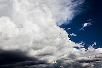 From left to right, storm clouds take over blue skies.  Background with room for text.