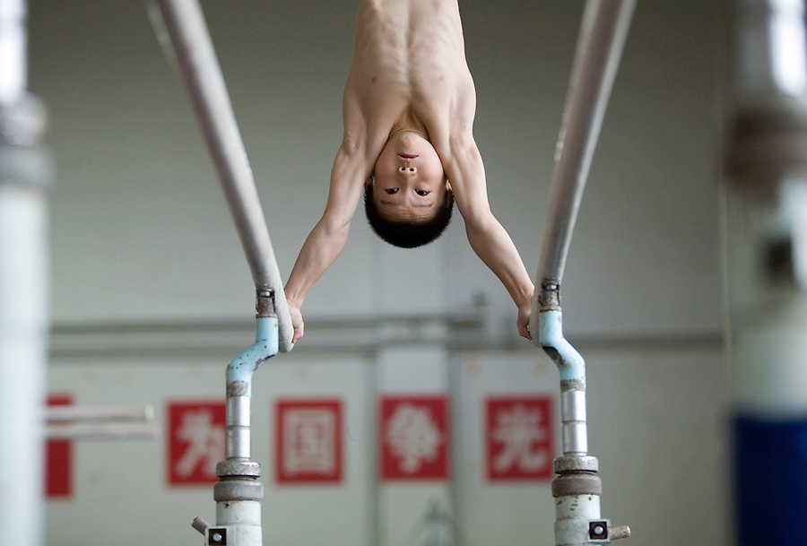 Eight year old Zhang Yu works on the even bars at a sports school to train gymnasts in Beijing.