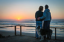 Couple with dog watching sunset over ocean from beach house at Yachats on the central Oregon coast.