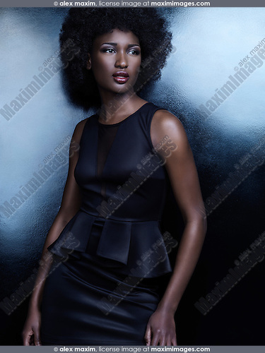 High fashion photo of a beautiful african american woman wearing a black dress on shiny background