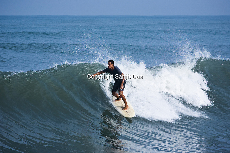 """Daruka Dasa, one of the Krishna devotees from the Kaliya Mardana Krishna Ashram is seen surfing on the Arabian Sea on the beach front of Mangalore, Karnataka, India.  ..Krishna devotees in the Gaudiya Vaishnava tradition of Hinduism, they are known collectively as the """"surfing swamis."""" The """"surfing ashram"""" is growing in popularity and surfing here is a form of meditation, a spiritual practice leading to heightened states of awareness."""