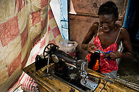 A Haitian dressmaker works in front of the house in the slum of Cité Soleil, Port-au-Prince, Haiti, 24 July 2008. Cité Soleil is considered one of the worst slums in the Americas, most of its 300.000 residents live in extreme poverty. Children and single mothers predominate in the population. Social and living conditions in the slum are a human tragedy. There is no running water, no sewers and no electricity. Public services virtually do not exist - there are no stores, no hospitals or schools, no urban infrastructure. In spite of this fact, a rent must be payed even in all shacks made from rusty metal sheets. Infectious diseases are widely spread as garbage disposal does not exist in Cité Soleil. Violence is common, armed gangs operate throughout the slum.