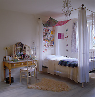 This simple white girl's bedroom features a romantic wrought-iron four poster bed