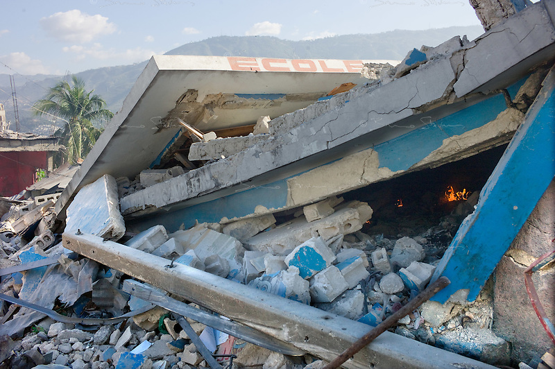 Port Au Prince, Haiti, Jan 27 2010.Dozens of children died when their school collapsed; inhabitants of the Fort National neighborhood try to set it on fire to burn the many bodies still decomposing under the rubble..
