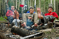 Photo story of Philmont Scout Ranch in Cimarron, New Mexico, taken during a Boy Scout Troop backpack trip in the summer of 2013. Photo is part of a comprehensive picture package which shows in-depth photography of a BSA Ventures crew on a trek.  In this photo BSA Venture Crew scouts work to dry out their feet around the campfire after heavy rains passed through the campsite in Baldy Town.<br /> <br /> The  Photo by travel photograph: PatrickschneiderPhoto.com