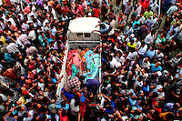 A crowd of people gathers around a pick up truck carrying the bodies of garment workers crushed to death in the collapsed Rana Plaza complex in Savar. The 8 storey building, which housed a number of garment factories employing over 3,000 workers, collapsed on 24 April 2013. By 29 April, at least 380 were known to have died while hundreds remained missing. Workers who were worried about going to work in the building when they noticed cracks in the walls were told not to worry by the building's owner, Mohammed Sohel Rana, who is a member of the ruling Awami League's youth front. He fled his home and tried to escape to neighbouring India after the building collapsed but was caught by police and brought back to Dhaka. Some of the factories working in the Rana Plaza building produce cheap clothes for various European retailers including Primark in the UK and Mango, a Spanish label. . /Felix Features