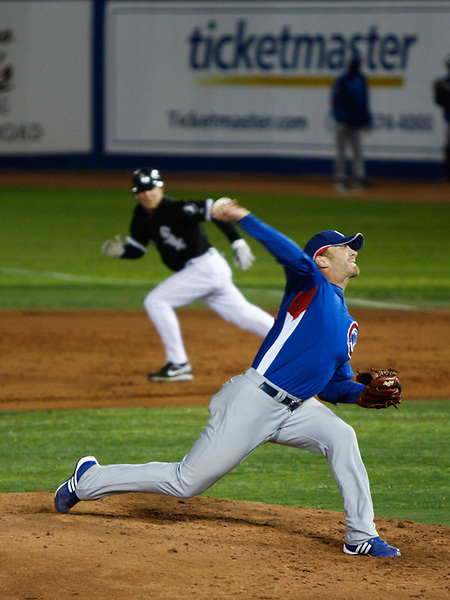 March 4, 2009. Las Vegas, NV: Chicago Cubs pitcher Ryan Dempster finishes his motion as a White Sox baserunner takes off toward second at Cashman Field.