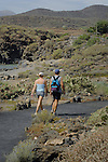 Couple walking  along track by the beach. South of Tenerife, Canary Islands.