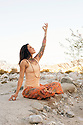 Yoga Woman outdoors touching earth and sky.