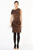 Model wears an asymmetric draped dress, and plume clutch, by Fiona Cibani, for the Ports 1961 Pre-Fall 2011 L'heure bleue collection, December 8, 2010.