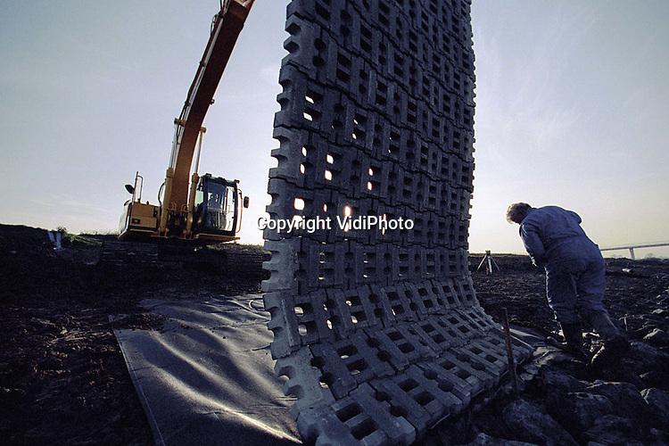 Foto: VidiPhoto..DRIEL - Het ziet er naar uit dat de aanleg van de negentien vispassages bij de stuwen van Driel niet op tijd -dus voor de Kerst- gereed komt. Er wordt op dit moment nog volop gewerkt aan het plaatsen van de stenen matten naast de vistrappen. De vispassages moeten de migratie van zeldzame soorten als zalm en zeeforel weer mogelijk maken. Het afgraven van het stuweiland, zodat de Rijn meer ruimte krijgt, is inmiddels voor 80 procent gereed. De totale kosten bedragen ongeveer 10 miljoen gulden.